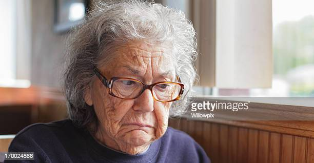 Sad Senior Woman Sitting in Restaurant