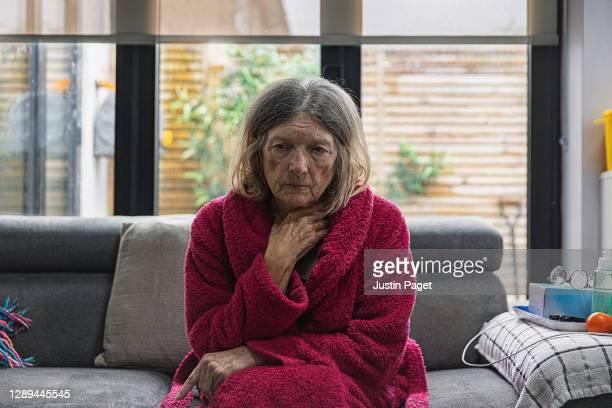 sad senior woman sitting on sofa - senior women stock pictures, royalty-free photos & images