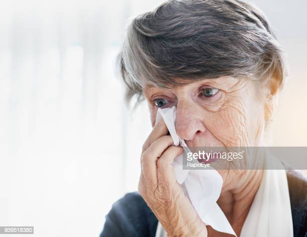 sad senior woman wiping eyes with tissue - rubbing stock pictures, royalty-free photos & images