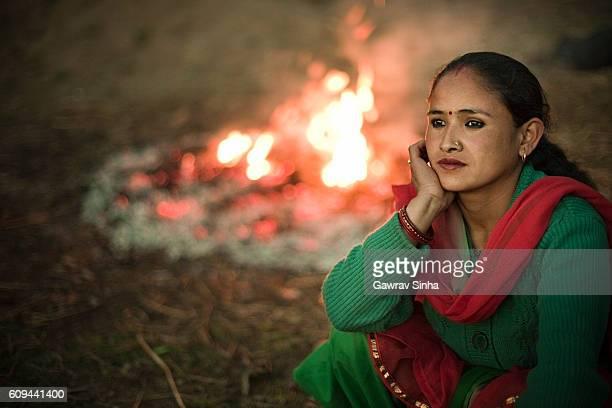 Sad serene Asian woman sitting outdoor near bonfire in evening.