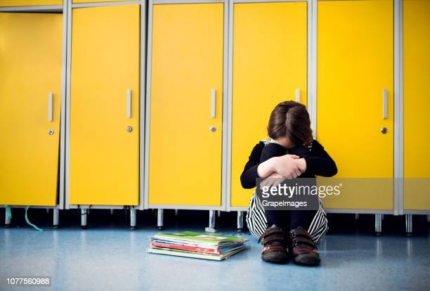 a sad small girl sitting on the floor at school, crying. - schoolgirl stock pictures, royalty-free photos & images