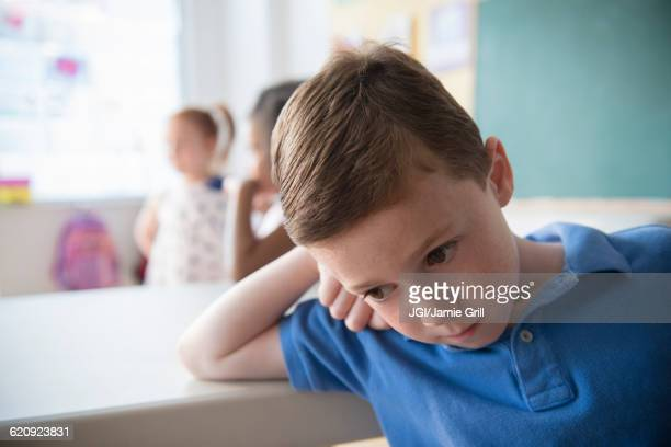 Sad student leaning on desk