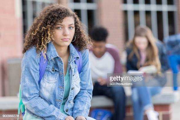 sad teen girl looking at camera outside high school - teenagers only stock pictures, royalty-free photos & images