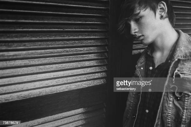 Sad teenage boy leaning against a wall
