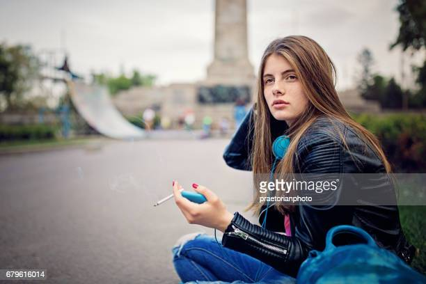 Sad teenage girl is sitting and smoking at the front of skateboard ramp
