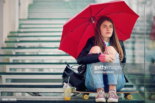Sad teenage girl is sitting sad on the stairs in a rainy day