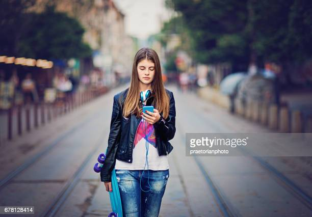 Sad teenage girl is walking in the middle of the street and texting