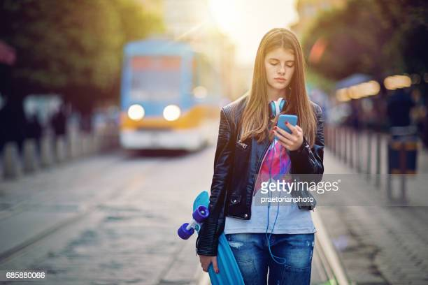 Sad teenage girl is walking on the street and texting at the front of sunset over the city