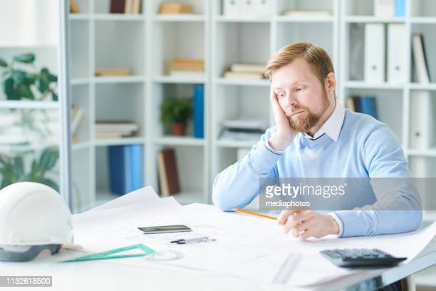 Sad tired young bearded engineer in blue sweater sitting at table and leaning head on hand while looking at blueprint and thinking about project