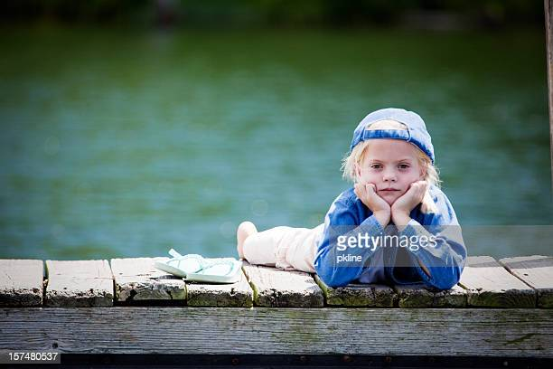 sad tomboy laying on dock - girl wear jeans and flip flops stock photos and pictures