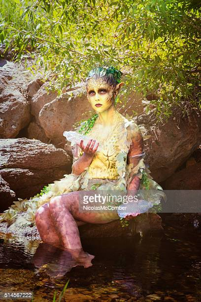 Sad water nymph holding plastic bottles in woods stream
