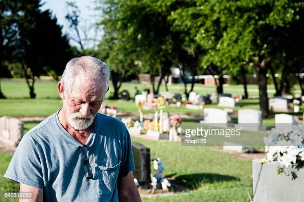 Sad widower, senior adult man visits cemetery.