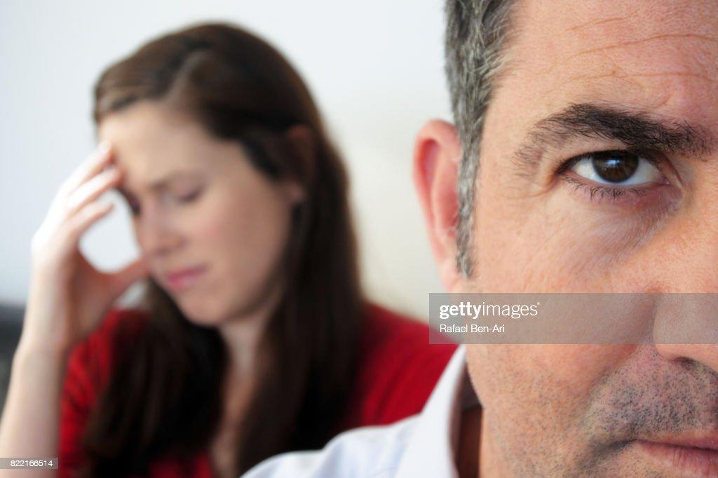 Sad wife sits behind her husband : Stock Photo