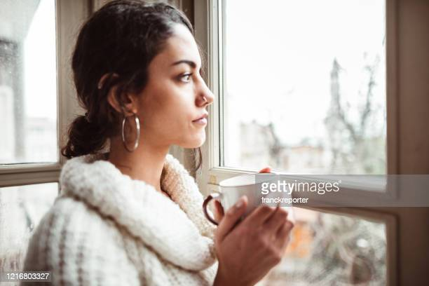 sad woman at home for the corona virus - coronavirus winter stock pictures, royalty-free photos & images