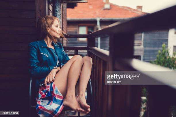 Traurige Frau auf dem Balkon mit Blick auf den Blick