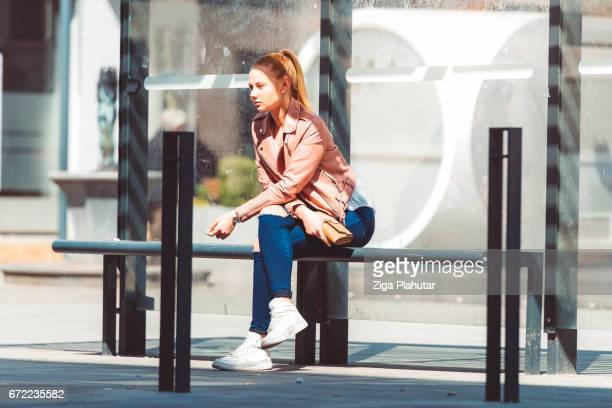 Sad woman at the bus shelter