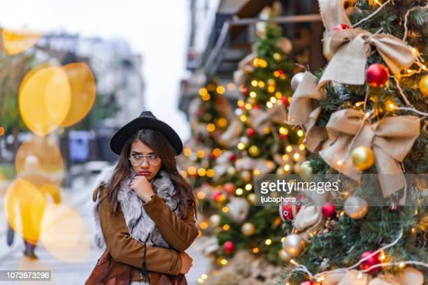 sad woman by the christmas tree - holiday stress stock pictures, royalty-free photos & images