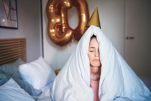 Sad woman celebrating her birthday, sitting on bed under blanket - gettyimageskorea