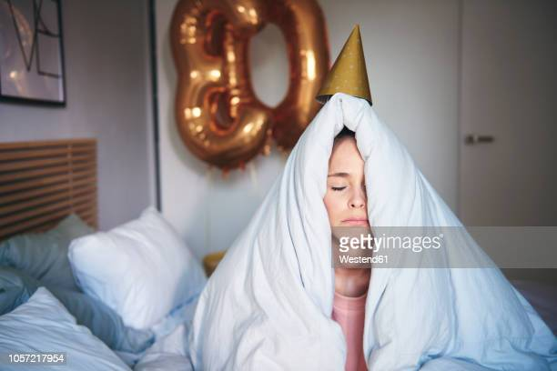 sad woman celebrating her birthday, sitting on bed under blanket - verdriet stockfoto's en -beelden