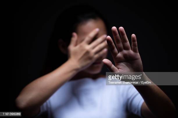 sad woman covering face with hand against black background - violence ストックフォトと画像