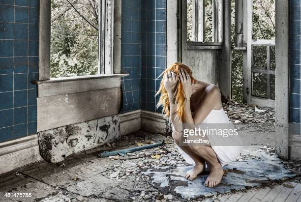 Sad Woman Crouching, Sobbing Amid Ruins