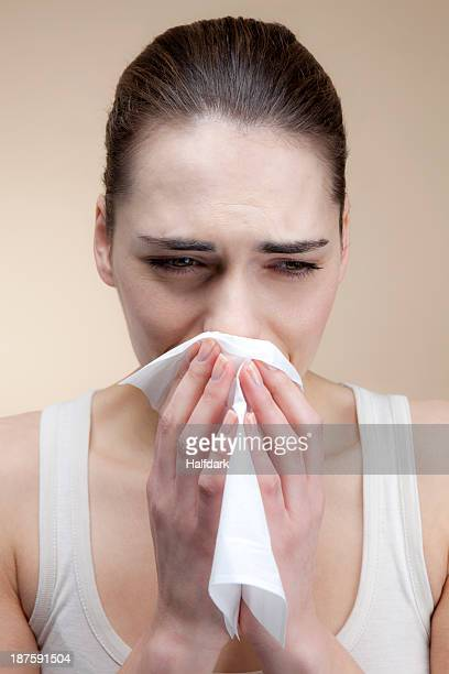 A sad woman crying and blowing her nose