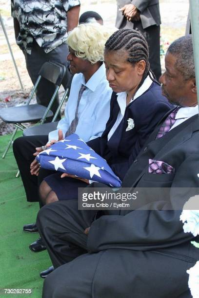 Sad Woman Holding American Flag While Sitting With Family And Friends At Funeral