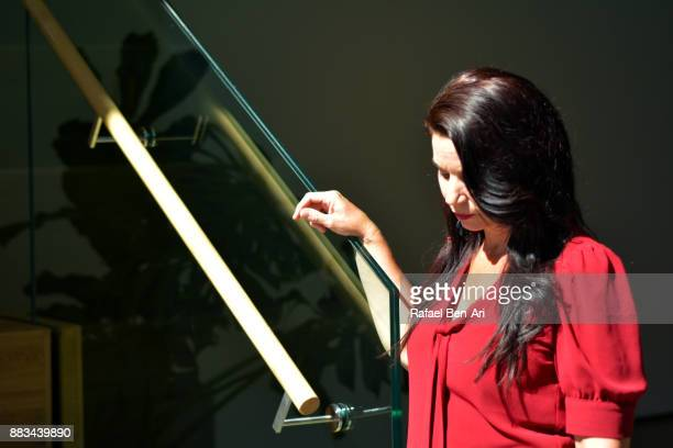 sad woman holds a stairs rail and looks down - down blouse stockfoto's en -beelden