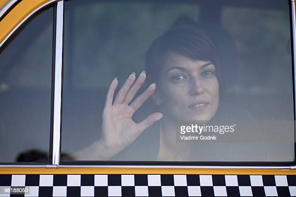 A sad woman in a taxi with her palm against the window