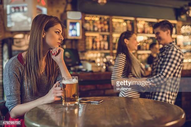 Triste Donna al bar guardando felice coppia sullo sfondo.
