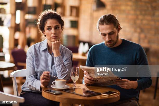 Sad woman in cafe with boyfriend who is reading newspaper.