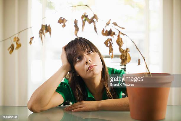 Sad woman looking at dead plant