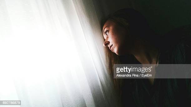 Sad Woman Looking Away While Sitting By Window Curtain At Home