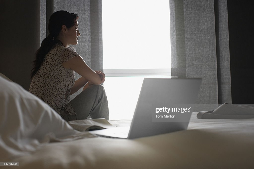 Sad woman looking out hotel window : Stock Photo