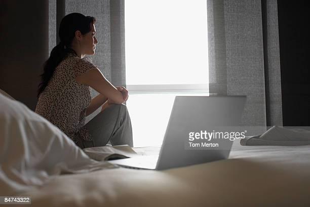 Mujer triste en la ventana mirando hacia fuera