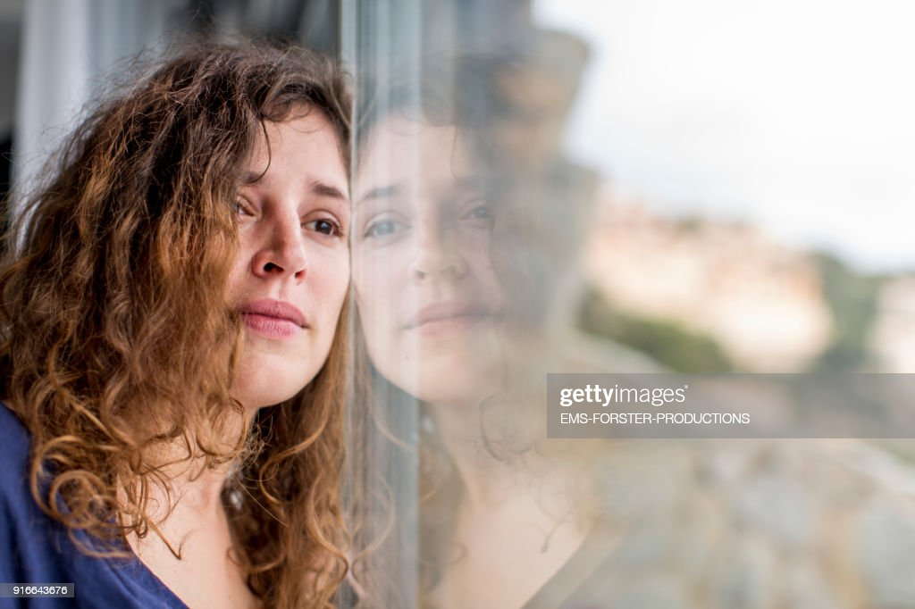 sad woman looking out of the window : Stock Photo