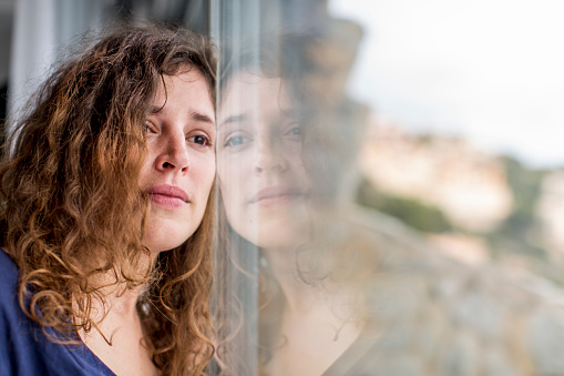 sad woman looking out of the window - gettyimageskorea