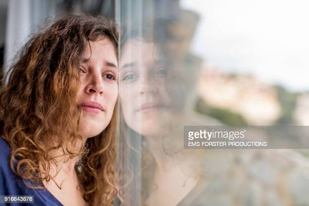 sad woman looking out of the window - grief fotografías e imágenes de stock