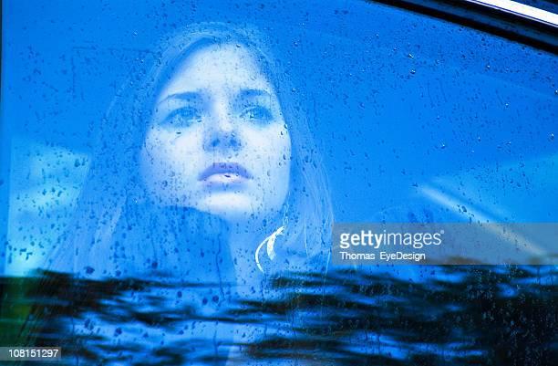 Traurige Frau Blick durchs Fenster im Regen