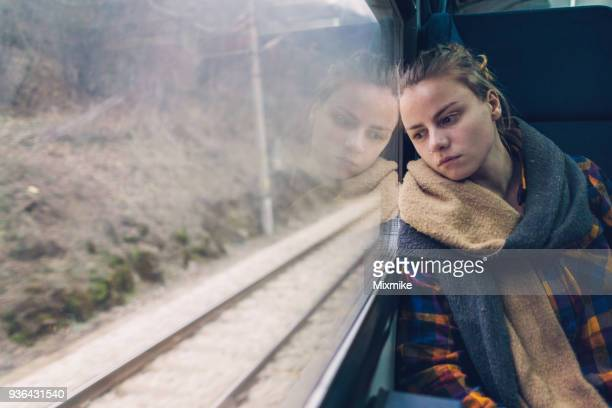 sad woman looking through the train window while travelling - shawl stock photos and pictures