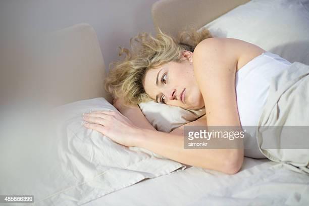 Traurige Frau liegen im Bett