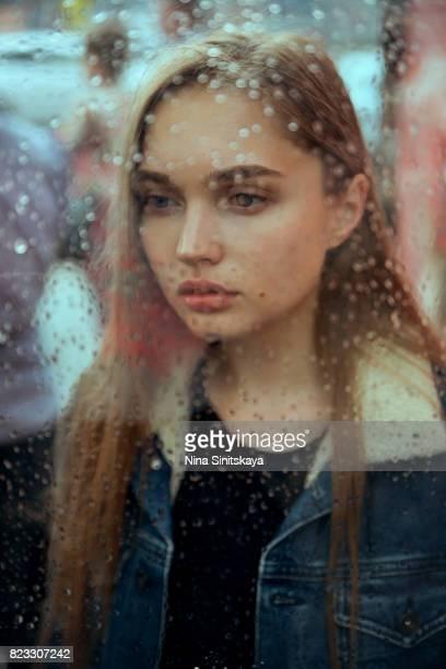 Sad woman near the window on rainy day