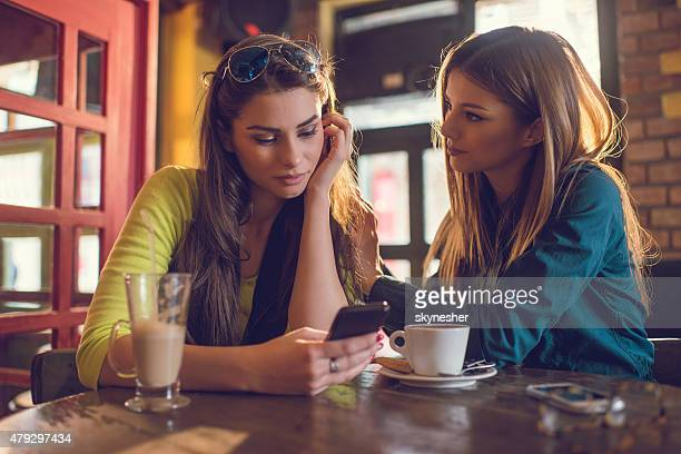 Sad woman reading text message to her friend in cafe.
