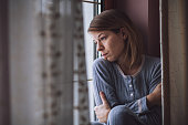Sad woman sitting by the window looking outside