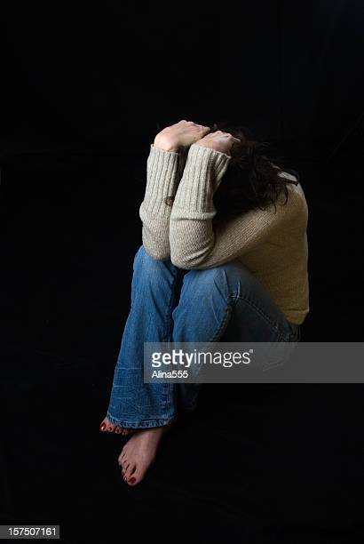 Sad woman sitting down covering her face