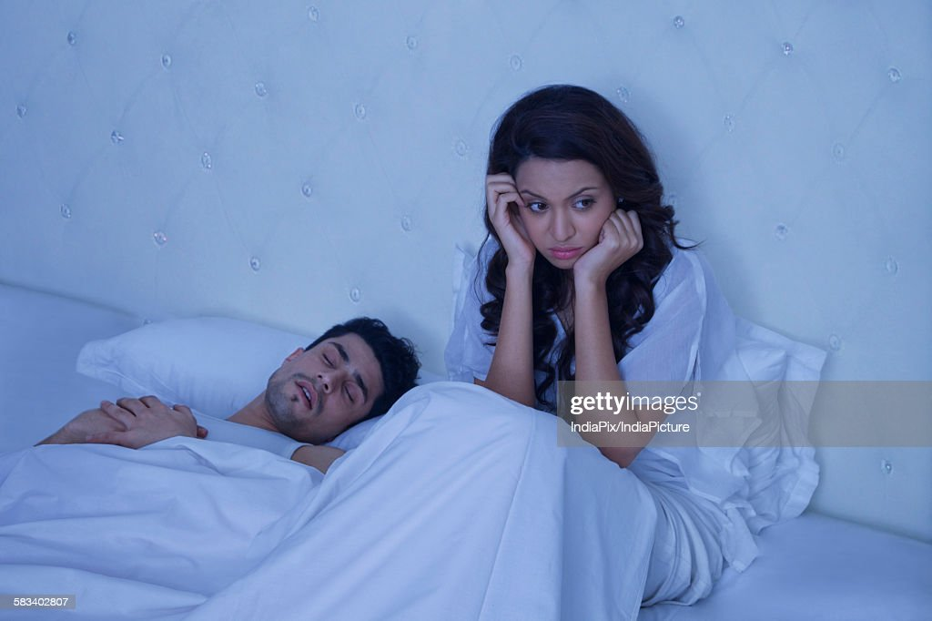 Sad woman sitting in bed with snoring man : Stock Photo