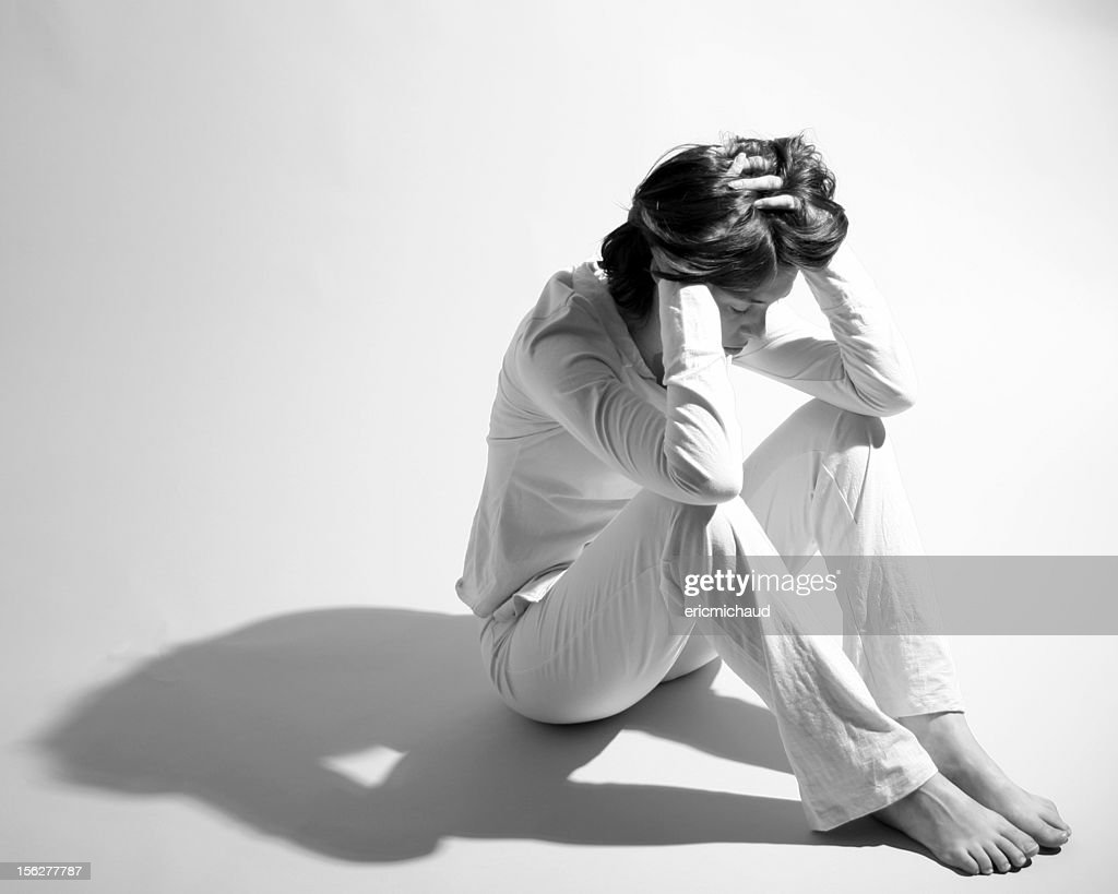 Sad Woman Sitting on Floor and Holding Head in Hands : Stock Photo