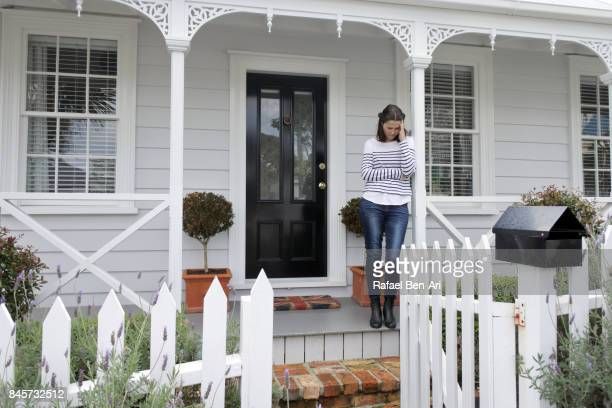 Sad woman stands in front of her home