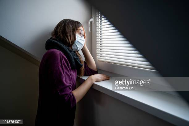 sad woman trapped in quarantine looking trough window daydreaming about going outdoors - stock photo - aplanar a curva imagens e fotografias de stock