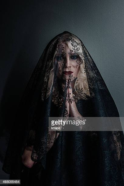 Sad woman under lace in grief praying